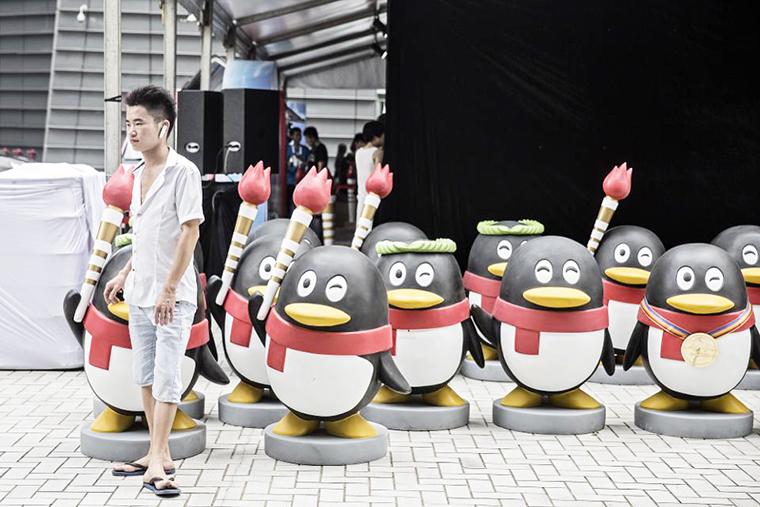 Một người đàn ông đứng bên cạnh bức tượng linh vật QQ bên ngoài trụ sở mới của Tencent