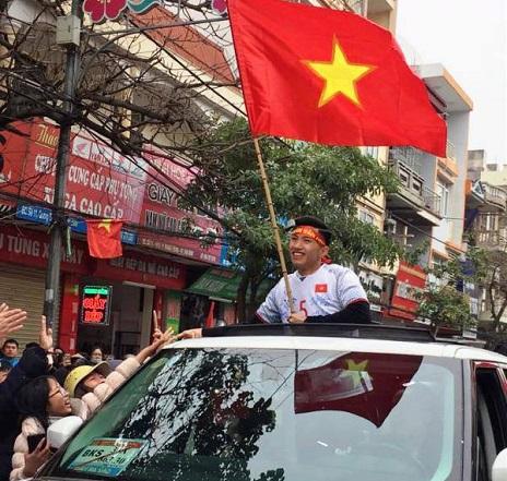 Cầu thủ Đoàn Văn Hậu tay cầm lá cờ Tổ quốc vẫy chào người hâm mộ